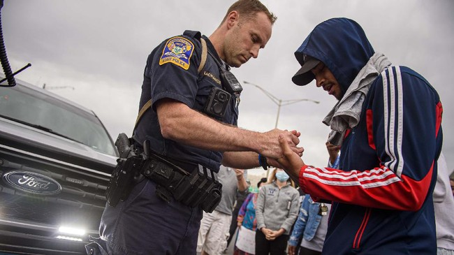 A Connecticut State Trooper prays with Nathaniel Swift, right, in the middle of Interstate 84 after it was closed down by hundreds protesting the death of George Floyd, Monday, June 1, 2020, in Hartford, Conn. Said Swift,