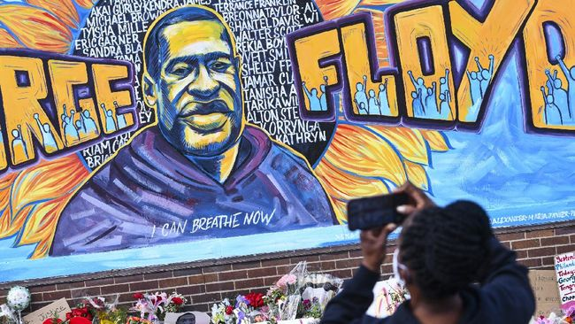 A person takes photographs of a mural in memory of George Floyd with flowers and other memorial items below, on a wall of the Cup Foods store at the corner of Chicago Avenue and East 38th Street, Friday, May 29, 2020, in Minneapolis. Protests over the death of Floyd in Minneapolis police custody have spread to other areas across the United States. (Dave Schwarz/St. Cloud Times via AP)