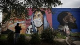 A woman photographs a mural of Cardi B that was updated by the artist Colton Valentine to include a face mask during the coronavirus outbreak in San Antonio, Monday, March 30, 2020. (AP Photo/Eric Gay)