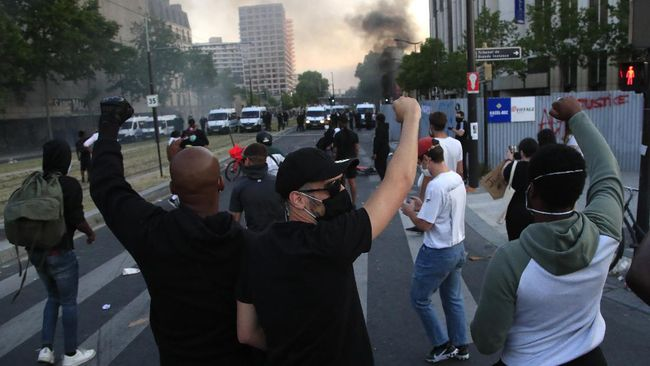 Protesters react in front of a police line as a barricade burns during a demonstration Tuesday, June 2, 2020 in Paris. Paris riot officers fired tear gas as scattered protesters threw projectiles and set fires at an unauthorized demonstration against police violence and racial injustice. Several thousand people rallied peacefully for two hours around the main Paris courthouse in homage to George Floyd and to Adama Traore, a French black man who died in police custody. (AP Photo/Michel Euler)