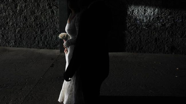 Haillie Bernal holds flowers while walking with Angel Martinez after getting married at Vegas Weddings, Friday, May 8, 2020, in Las Vegas. (AP Photo/John Locher)