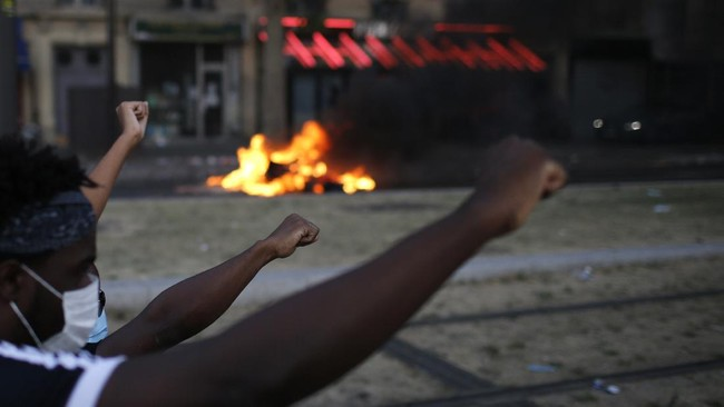Protesters raises their fist during a demonstration Tuesday, June 2, 2020. Paris riot officers fired tear gas as scattered protesters threw projectiles and set fires at an unauthorized demonstration against police violence and racial injustice. Several thousand people rallied peacefully for two hours around the main Paris courthouse in homage to George Floyd and to Adama Traore, a French black man who died in police custody. (AP Photo/Rafael Yaghobzadeh)