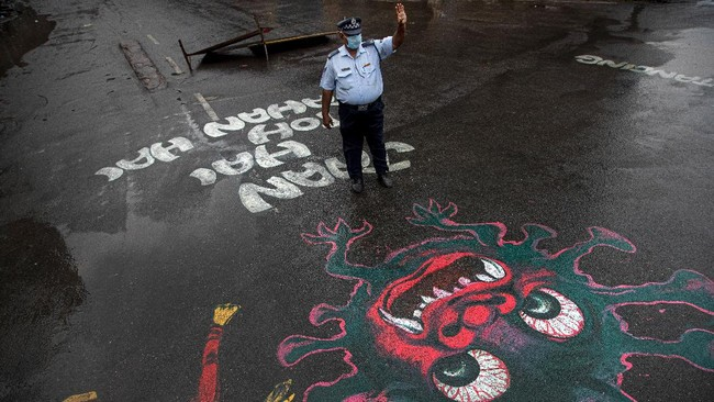 An Indian traffic policeman stands next to an artwork displayed on a road to create awareness about coronavirus during lockdown in Gauhati, India, Wednesday, April 15, 2020. (AP Photo/Anupam Nath)