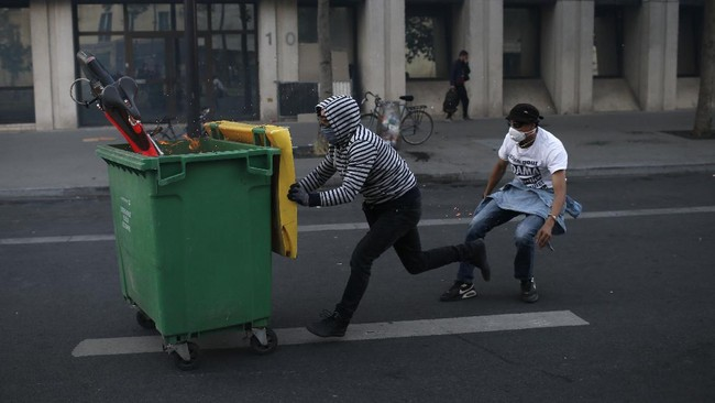 Protesters pull a garbage bin during a demonstration Tuesday, June 2, 2020. Paris riot officers fired tear gas as scattered protesters threw projectiles and set fires at an unauthorized demonstration against police violence and racial injustice. Several thousand people rallied peacefully for two hours around the main Paris courthouse in homage to George Floyd and to Adama Traore, a French black man who died in police custody. (AP Photo/Rafael Yaghobzadeh)