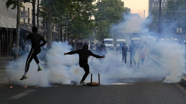 Protester kick in tear gas canisters during a demonstration Tuesday, June 2, 2020 in Paris. Thousands of people defied a police ban and converged on the main Paris courthouse for a demonstration to show solidarity with U.S. protesters and denounce the death of a black man in French police custody. The demonstration was organized to honor Frenchman Adama Traore, who died shortly after his arrest in 2016, and in solidarity with Americans demonstrating against George Floyd's death. (AP Photo/Michel Euler)