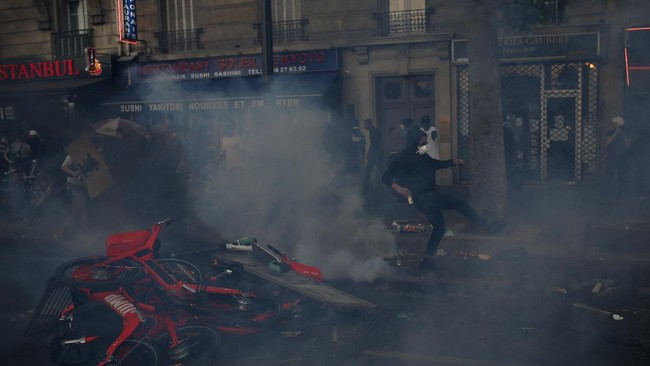 A protester kicks into a tear gas canister during a demonstration Tuesday, June 2, 2020. Paris riot officers fired tear gas as scattered protesters threw projectiles and set fires at an unauthorized demonstration against police violence and racial injustice. Several thousand people rallied peacefully for two hours around the main Paris courthouse in homage to George Floyd and to Adama Traore, a French black man who died in police custody. (AP Photo/Rafael Yaghobzadeh)