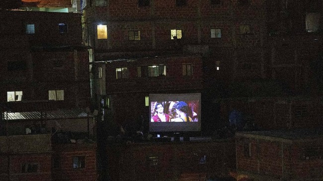The film Aladdin is projected on a screen set up on the roof of a home in the Petare neighborhood of Caracas, Venezuela, Monday, June 1, 2020. A neighborhood group called The Download Zone set up the movie as a free entertainment option for families cooped up since mid-March under the COVID-19 quarantine. (AP Photo/Ariana Cubillos)