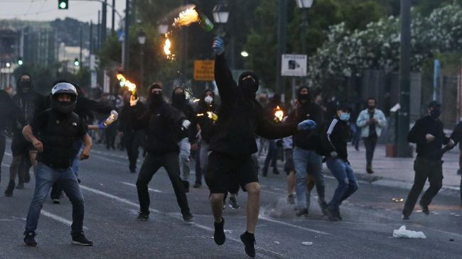 Masked protesters hurl petrol bombs towards the direction of riot police officers during minor scuffles outside the U.S. embassy in Athens, Wednesday, June 3, 2020, following a demonstration over the death of George Floyd, a black man who died after being restrained by Minneapolis police officers on May 25. Greek police have fired tear gas to disperse youths who attacked them following an otherwise peaceful demonstration by about 4,000 people. (AP Photo/Lefteris Pitarakis)