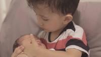 <p>James merupakan anak sulung yang sudah menunjukkan rasa sayang pada adiknya sejak kecil, Bunda. Seperti di foto ini, ia memeluk Iona ketika baru lahir. (Foto: Instagram @dahliachr)</p>
