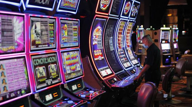 In this May 21, 2020, file photo, a worker looks over an electronic slot machine as chairs have been removed from some machines to maintain social distancing between players at a closed Caesars Palace hotel and casino in Las Vegas. Cards will be cut, dice will roll and jackpots jingle when casinos in Las Vegas and Nevada begin reopening at 12:01 a.m. Thursday, June 4. There will be big splashes, even amid ongoing unrest, and big hopes for recovery from an unprecedented and expensive closure prompted by the coronavirus pandemic. (AP Photo/John Locher, File)