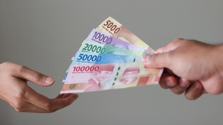 man hand show rupiah money on white background