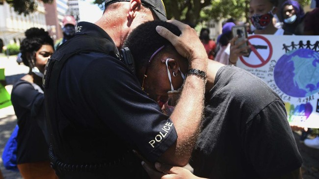 A police officer and a demonstrator hug as people gather in Shreveport, La., Sunday, May 31, 2020. They marched to the Caddo Parish Courthouse for Black Lives Matter. (Henrietta Wildsmith/The Shreveport Times via AP)