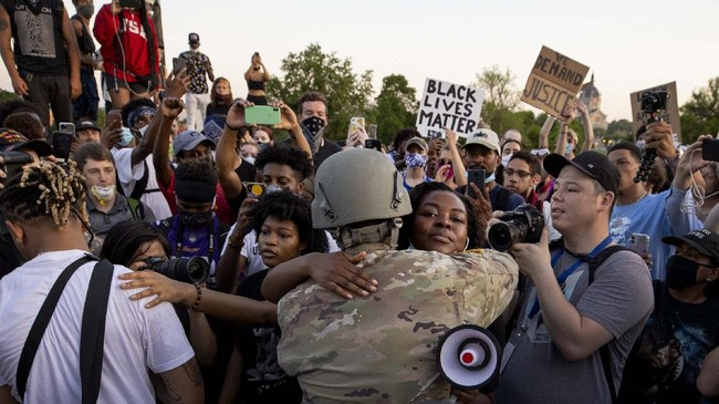 National Guard Master Sgt, Acie Matthews Jr. hugs a protester at the State Capitol in St. Paul, Minn., Monday, June 1, 2020, during protests over the death of George Floyd, who died May 25 after being restrained by Minneapolis police. (Carlos GonzalezStar Tribune via AP)