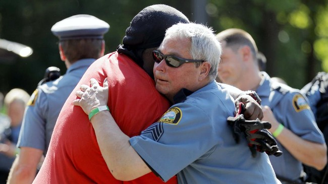 Gemini Stone Pollard, left, hugs a police officer Monday, June 1, 2020, in St. Paul, Minn. Protests continued following the death of George Floyd, who died after being restrained by Minneapolis police officers on Memorial Day. (AP Photo/Julio Cortez)