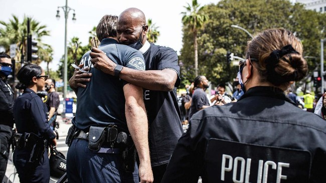 Pastor Calvin Sparks, of Life Pavilion in Carson, hugs LAPD officers after some officers took a knee with clergy and marchers at LAPD Headquarters during a demonstration demanding justice for George Floyd, Tuesday, June 2, 2020 in Los Angeles, Floyd, a black man, died after being restrained by Minneapolis police officers on May 25.  (Sarah Reingewirtz/The Orange County Register via AP)