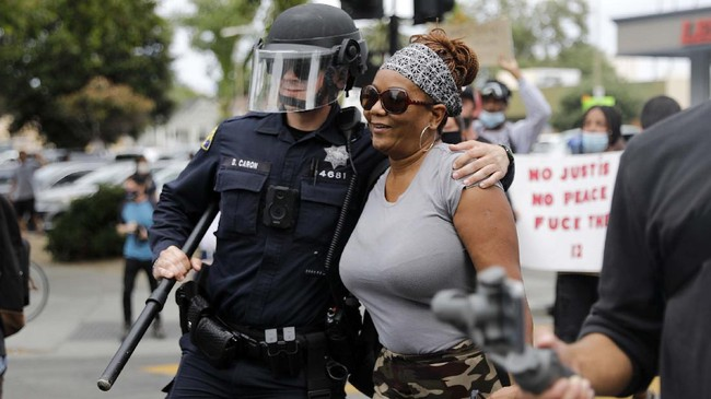 A San Jose Police officer gives a protester a hug during a protest over the death of George Floyd outside of San Jose City Hall in downtown San Jose, Calif., on Sunday, May 31, 2020. (Nhat V. Meyer/Bay Area News Group)