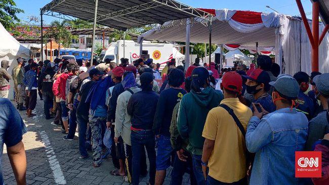 Warga Surabaya antre berdesakan tanpa menerapkan protokol kesehatan seperti physical distancing, dan penggunaan masker, saat mengikuti rapid test yang diadakan Badan Intelijen Negara (BIN), Kamis (4/6).