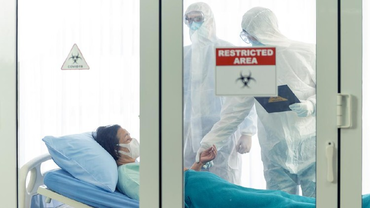 Doctor examines corona or covid-19 virus patient in the clean room with covid 19 and restricted area sign in front of the room
