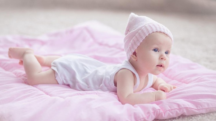 Cute playfull baby girl, wearing pink winter hat, lying at her tommy on a pink comforter on the floor. She's curious about her room interior.