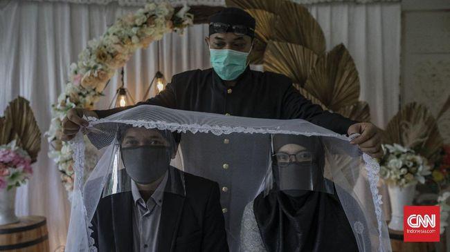 Suasana akad nikah di Kantor Urusan Agama (KUA) kecamatan Ciracas, Jakarta, Sabtu, 6 Juni 2020. Sesuai dengan SE Nomor 15 Tahun 2020 Tentang Panduan Penyelenggaraan Kegiatan di Rumah Ibadah Dalam Mewujudkan Masyarakat Produktif dan Aman Covid-19 di Masa Pandemi, calon pengantin diharuskan mengikuti protokol kesehatan seperti menggunakan masker dan sarung tangan. CNN Indonesia/Bisma Septalisma