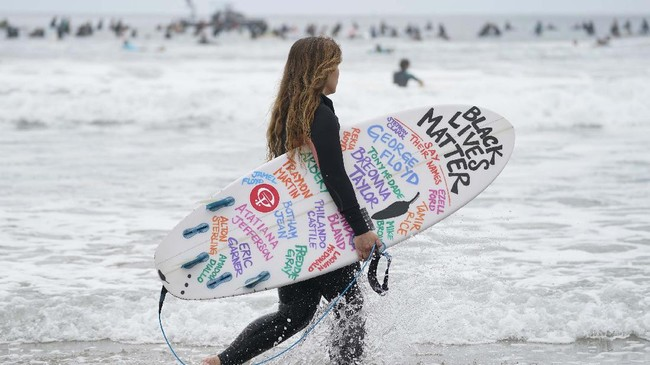 Surfers participate in a paddle out ceremony at