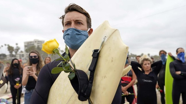 Robert Huffman holds his surfboard and a rose as he participates in a paddle out ceremony at
