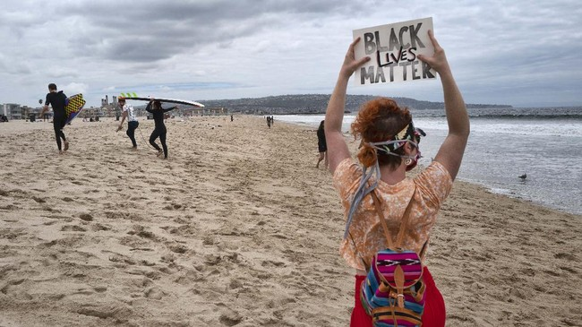 Shawna Ventimiglia, holds a sign in support of a local group of surfers during a traditional paddle out ceremony in Hermosa Beach in support of Black Lives Matter over the death of George Floyd in Los Angeles, Friday June 5, 2020. People protest over the death of George Floyd after he died in police custody in Minneapolis on May 25. (AP Photo/Richard Vogel)