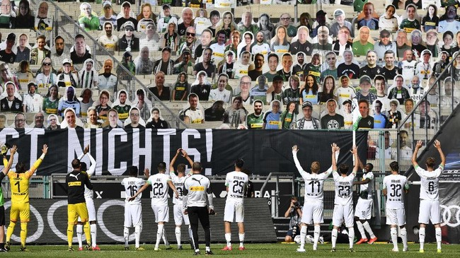 Moenchengladbach players celebrate in front of the cardboards with photos of Moenchengladbach fans displayed on the stands at the end of the German Bundesliga soccer match between Borussia Moenchengladbach and Union Berlin in Moenchengladbach, Germany, Sunday, May 31, 2020. The German Bundesliga becomes the world's first major soccer league to resume after a two-month suspension because of the coronavirus pandemic. (AP Photo/Martin Meissner, Pool)