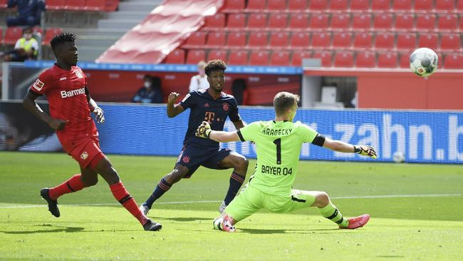 Kingsley Coman of Munich scores his team's first goal past goalkeeper Lukas Hradecky of Leverkusen during the German Bundesliga soccer match between Bayer Leverkusen and Bayern Munich in Leverkusen, Germany, Saturday, June 6, 2020. (Matthias Hangst, Pool via AP)