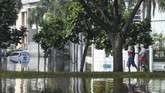 Warga melintas di Kompleks Pantai Mutiara yang tergenang banjir rob di Penjaringan, Jakarta, Minggu (7/6/2020). Banjir di kawasan tersebut diduga akibat adanya tanggul yang jebol saat naiknya permukaan air laut di pesisir utara Jakarta. ANTARA FOTO/Hafidz Mubarak A/foc.