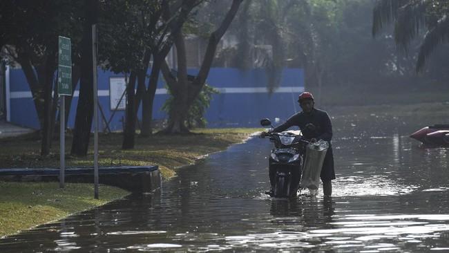 Pengendara mendorong motornya yang mogok saat melintasi banjir rob di Kompleks Pantai Mutiara, Penjaringan, Jakarta, Minggu (7/6/2020). Banjir di kawasan tersebut diduga akibat adanya tanggul yang jebol saat naiknya permukaan air laut di pesisir utara Jakarta. ANTARA FOTO/Hafidz Mubarak A/foc.