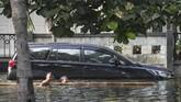 Dua anak bermain air saat banjir rob menggengangi Kompleks Pantai Mutiara, Penjaringan, Jakarta, Minggu (7/6/2020). Banjir di kawasan tersebut diduga akibat adanya tanggul yang jebol saat naiknya permukaan air laut di pesisir utara Jakarta. ANTARA FOTO/Hafidz Mubarak A/foc.