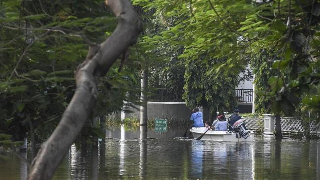 Warga menggunakan perahu untuk melintasi banjir rob di Kompleks Pantai Mutiara, Penjaringan, Jakarta, Minggu (7/6/2020). Banjir di kawasan tersebut diduga akibat adanya tanggul yang jebol saat naiknya permukaan air laut di pesisir utara Jakarta. ANTARA FOTO/Hafidz Mubarak A/foc.