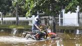 Pengendara motor melintas saat banjir rob menggenangi Kompleks Pantai Mutiara, Penjaringan, Jakarta, Minggu (7/6/2020). Banjir di kawasan tersebut diduga akibat adanya tanggul yang jebol saat naiknya permukaan air laut di pesisir utara Jakarta. ANTARA FOTO/Hafidz Mubarak A/foc.