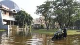 Pengendara motor menata barang bawaannya di atas motor yang mogok akibat banjir rob di Kompleks Pantai Mutiara, Penjaringan, Jakarta, Minggu (7/6/2020). Banjir di kawasan tersebut diduga akibat adanya tanggul yang jebol saat naiknya permukaan air laut di pesisir utara Jakarta. ANTARA FOTO/Hafidz Mubarak A/foc.