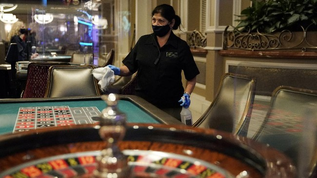 Eloina Marquez cleans at a roulette table at the reopening of the Bellagio hotel and casino Thursday, June 4, 2020, in Las Vegas. Casinos in Nevada were allowed to reopen on Thursday for the first time after temporary closures as a precaution against the coronavirus. (AP Photo/John Locher)