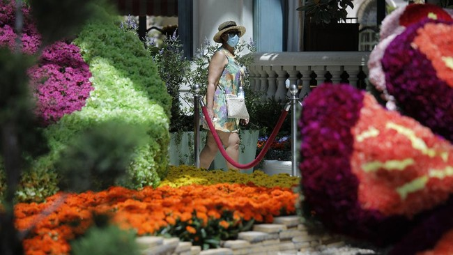 A woman in a mask walks through the Conservatory & Botanical Gardens at the reopening of the Bellagio hotel and casino Thursday, June 4, 2020, in Las Vegas. Casinos in Nevada were allowed to reopen on Thursday for the first time after temporary closures as a precaution against the coronavirus. (AP Photo/John Locher)