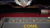 A craps dealer waits for customers before the reopening of the D Las Vegas hotel and casino, Wednesday, June 3, 2020, in Las Vegas. Casinos were allowed to reopen early Thursday after temporary closures as a precaution against the coronavirus. (AP Photo/John Locher)