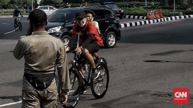 Warga memadati area car free day (CFD) di sepanjang jalan Sudirman hingga Thamrin, Jakarta Pusat meski secara resmi area tersebut belum bebas kendaraan bermotor di masa transisi Pembatasan Sosial Berskala Besar (PSBB) Jakarta, warga mayoritas  berolahraga sepeda. Minggu (7/6/2020). CNN Indonesia/Andry Novelino