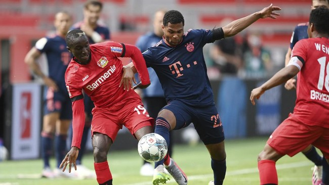Serge Gnabry, right, from Munich in action against Moussa Diaby from Leverkusen during the German Bundesliga soccer match between Bayer Leverkusen and Bayern Munich in Leverkusen, Germany, Saturday, June 6, 2020. (Matthias Hangst, Pool via AP)