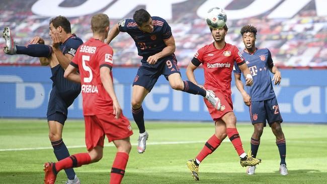 Robert Lewandowski, center, of Municg scores his team's fourth during the German Bundesliga soccer match between Bayer Leverkusen and Bayern Munich in Leverkusen, Germany, Saturday, June 6, 2020. (Matthias Hangst, Pool via AP)