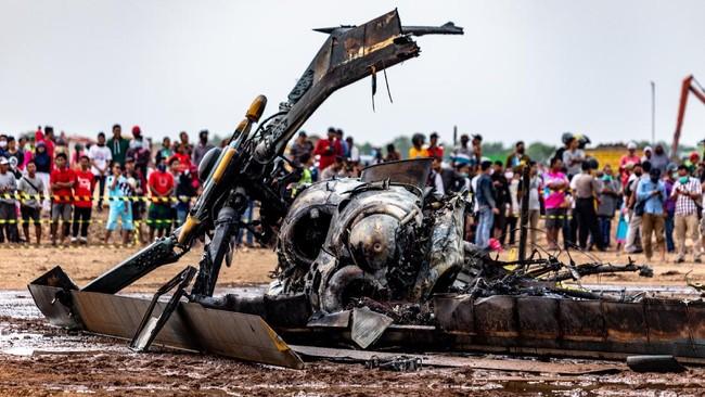Sejumlah warga menyaksikan bangkai helikopter yang jatuh di Kawasan Industri Kendal (KIK), Kabupaten Kendal, Jawa Tengah, Sabtu (6/6/2020). Belum diketahui penyebab jatuhnya helikopter jenis MI-17 bernomor registrasi HA 5141 milik TNI-AD yang mengakibatkan empat awak tewas dan lima awak lainnya dilarikan ke rumah sakit. ANTARA FOTO/Aji Styawan/WSJ.
