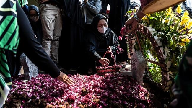 Istri almarhum Lettu Wisnu Tia Aruni, Yuanita Rahmawati menabur bunga pada pusara suaminya usai prosesi pemakaman di Tempat Pemakaman Umum Kembangarum (Bergota II), Semarang, Jawa Tengah, Minggu (7/6/2020). Lettu Wisnu Tia Aruni merupakan satu dari empat prajurit TNI AD yang tewas dalam insiden kecelakaan helikopter MI-17 V5 di Kawasan Industri Kendal (KIK), Jateng pada Sabtu (6/6/2020). ANTARA FOTO/Aji Styawan/foc.