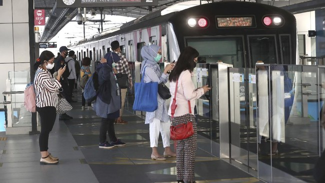 Passengers wearing face masks stand near a MRT train station in Jakarta, Indonesia, Monday, June 8, 2020. Indonesia's capital of Jakarta, the city hardest hit by the new coronavirus, has partly reopened after two months of partial lockdown as the world's fourth most populous nation braces to gradually reopen its economy. (AP Photo/Tatan Syuflana)