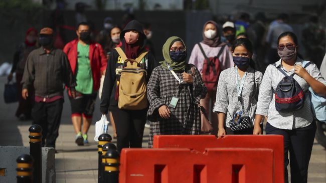 People wear face masks as a precaution against the new coronavirus as they walk on a street in Jakarta, Indonesia Monday, June 8, 2020. Indonesia's capital of Jakarta, the city hardest hit by the new coronavirus, has partly reopened after two months of partial lockdown as the world's fourth most populous nation braces to gradually reopen its economy. (AP Photo/Achmad Ibrahim)
