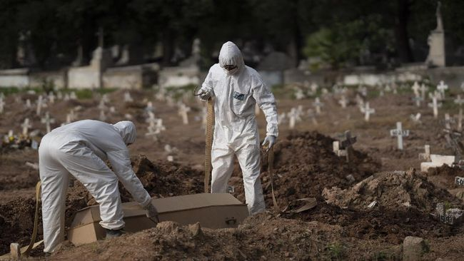 Cemetery workers in protective clothing maneuver the coffin of 57-year-old Paulo Jose da Silva, who died from the new coronavirus, in Rio de Janeiro, Brazil, Friday, June 5, 2020. According to Monique dos Santos, her stepfather mocked the existence of the virus, didn't use a mask, didn't take care of himself, and wanted to shake hands with everybody.