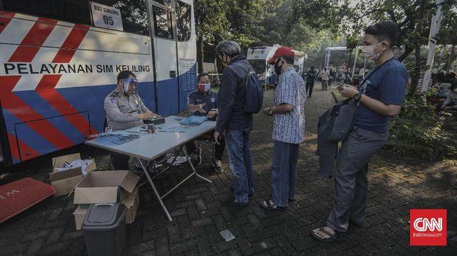 Warga antre mengurus perpanjangan Surat Ijin Mengemudi (SIM) di layanan SIM keliling di Kawasan Masjid Agung At-Tin, Jakarta, Rabu, 10 Juni 2020. Untuk menghindari antrean panjang, pihak Satlantas membatasi jumlah layanan perpanjangan SIM, yakni sebanyak 300 orang per hari, dan dibagi menjadi 3 gelombang. CNN Indonesia/Bisma Septalisma