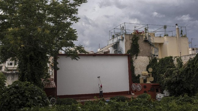 In this Friday May 29, 2020 photo Christina Tsouta, cleans the screen at the Zephyros open-air cinema that specializes in films from past decades in Athens' central Petralona district. (AP Photo/Petros Giannakouris)