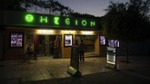 In this Thursday June 4 , 2020 photo passers by looks at movie notices outside the Thision outdoor summer cinema where moviegoers watch films under the ancient Acropolis. Cine Thision is one of the oldest open-air movie theaters in Athens, built in 1935. (AP Photo/Petros Giannakouris)