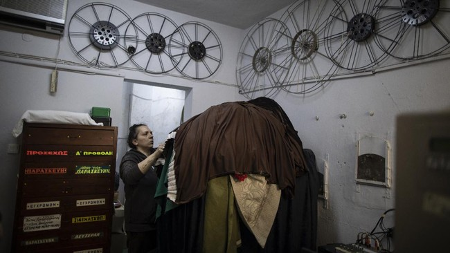 In this Sunday May 31, 2020 photo, owner Meri Panou operates her equipment inside a projection booth at the Dionisia open-air cinema in Athens. Like so much else, Greece's open-air cinemas, where patrons can enjoy a movie in the flower-scented moonlight with a drink, a snack and even a smoke, have been hard-hit by lockdown measures. Under the country's partial reopening, open-air cinemas started operating on June 1, a month late and with considerable restrictions. (AP Photo/Petros Giannakouris